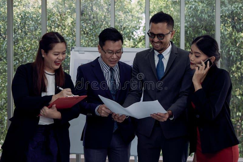 Affärsman fyra och kvinnaanseende och kontroll som tillsammans drar i mötesrum arkivbilder
