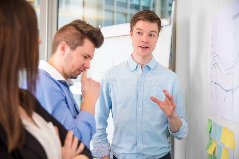 Affärsman Gesturing While Communicating med kollegor arkivbild
