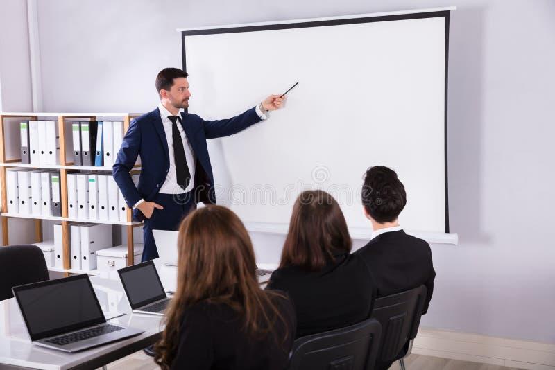 Affärsman Giving Presentation To hans kollega royaltyfri bild
