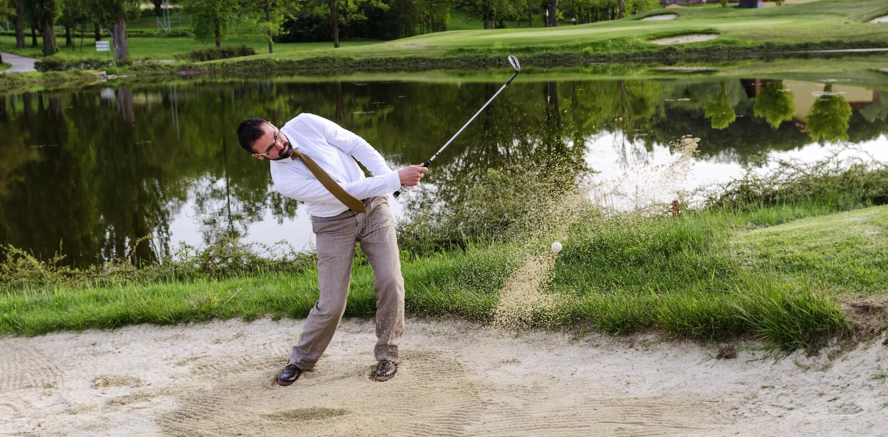 Affärsman Golfer i sandfälla royaltyfria bilder