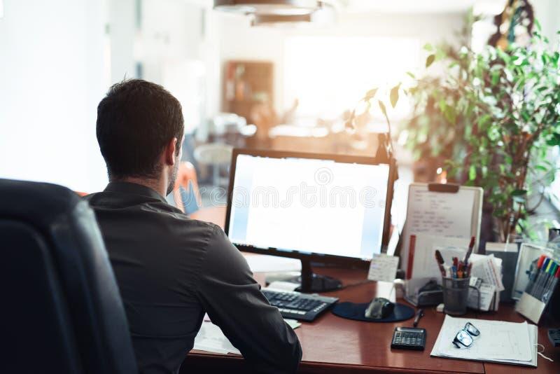 Affärsman hårt på arbete på en dator i ett kontor royaltyfria bilder
