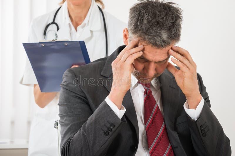 Affärsman Having Headache för doktor Standing Behind The arkivbilder