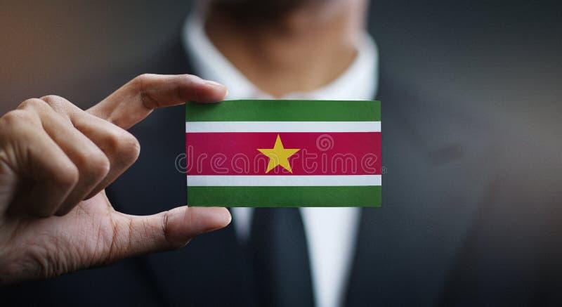 Affärsman Holding Card av den Surinam flaggan fotografering för bildbyråer