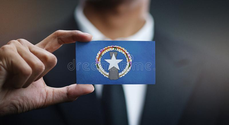 Affärsman Holding Card Northern Mariana Islands Flag royaltyfri bild
