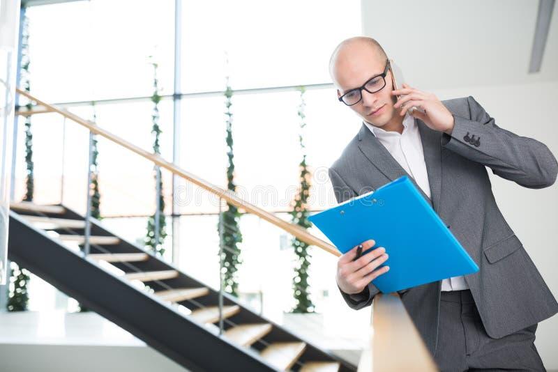 Affärsman Holding Clipboard While som i regeringsställning använder Smartphone royaltyfri fotografi