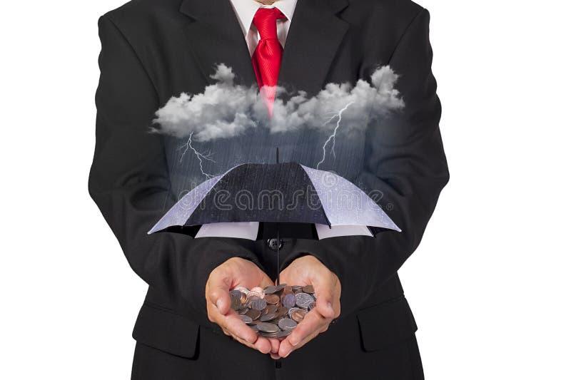 Affärsman Holding ett skyddande paraply över en finansiell investering under stormiga dagar arkivbilder