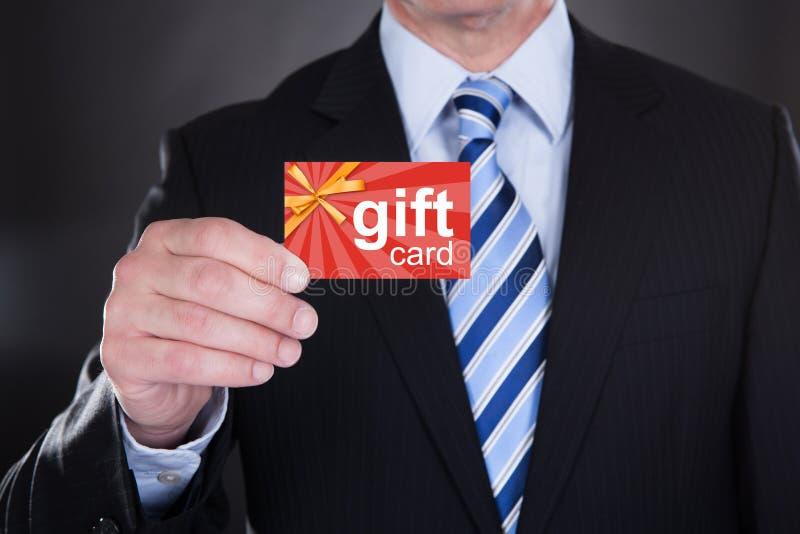 Affärsman Holding Gift Card royaltyfri foto