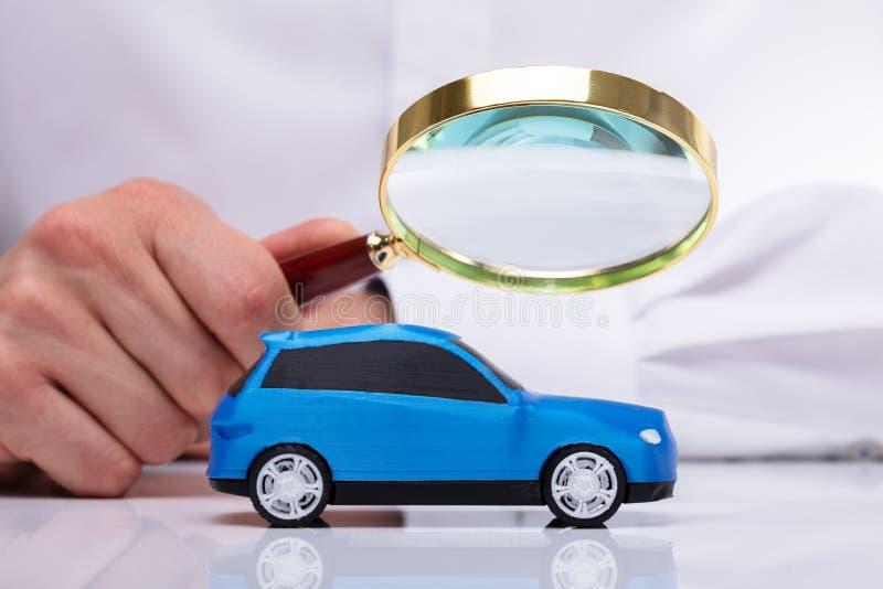 Affärsman Holding Magnifying Glass över bilen fotografering för bildbyråer