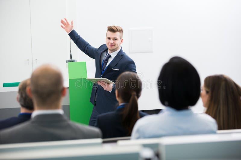 Affärsman Holding Tablet Computer, medan ge presentation till royaltyfri foto