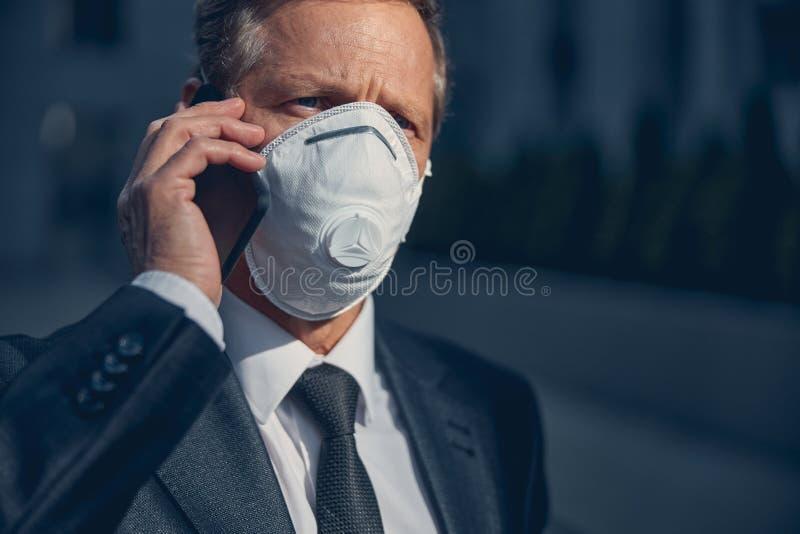 Affärsman i antiviral respirator som talar på mobiltelefon utomhus arkivfoton