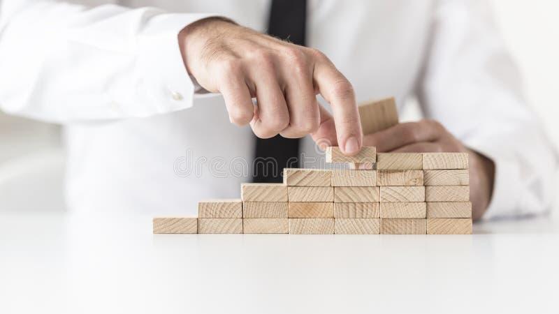 Affärsman i den vita skjortan som bygger en graf eller en stege av framgång arkivfoton