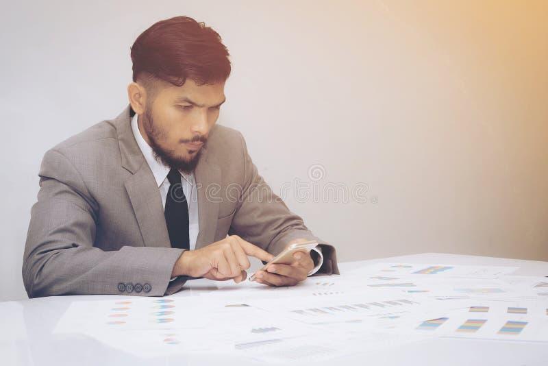 Affärsman i dräkt genom att använda på smartphonen i regeringsställning arkivfoton