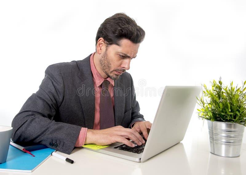 Affärsman i dräkt- och bandsammanträde på kontorsskrivbordet som arbetar på datorbärbara datorn som ser koncentrerad och eftertän arkivfoton