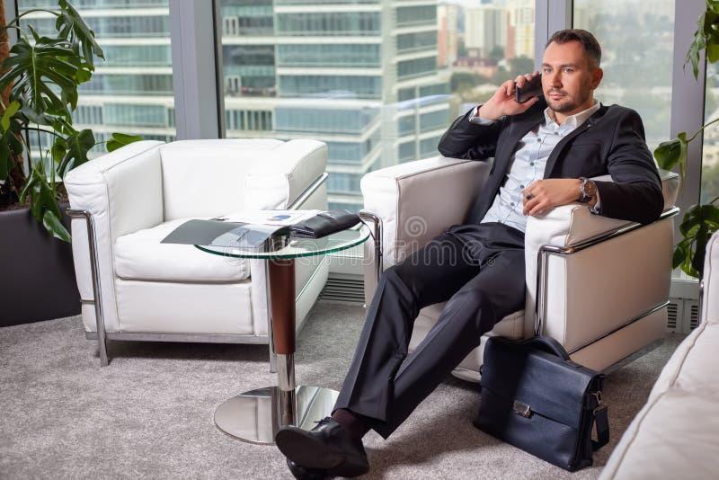 Affärsman i dräkt som talar på mobiltelefonsammanträde i en lätt stol royaltyfria foton