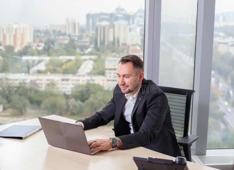 Affärsman i dräkten som arbetar på bärbara datorn arkivbilder