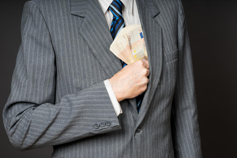 Affärsman i dräkten som sätter sedlar i hans omslagsbröstfack Affärsmannen är hållande kassa, bunten av femtio euro pengar Pers royaltyfri fotografi