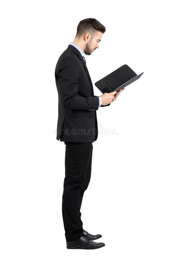 Affärsman i dräktläsningdokument eller avtalssidosikt royaltyfri foto