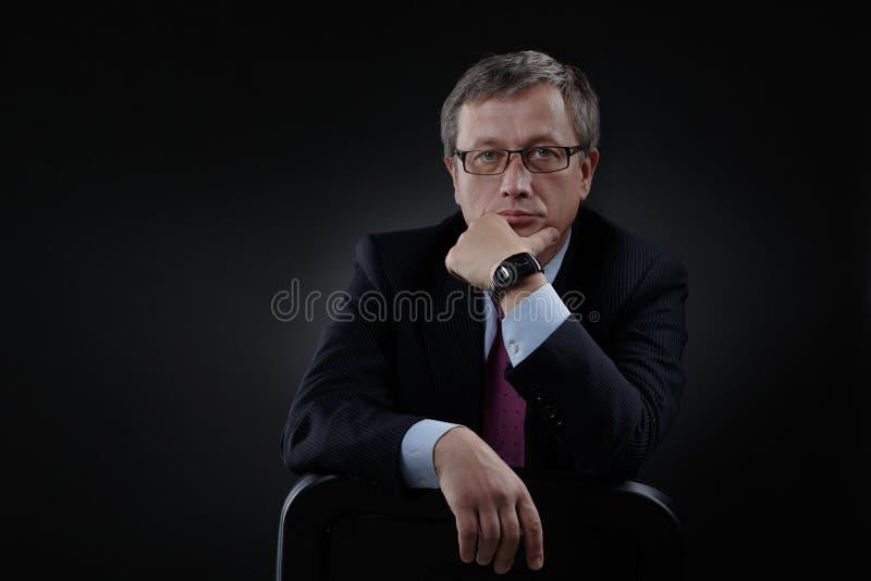 Affärsman i en dräkt på en mörk bakgrund royaltyfri bild