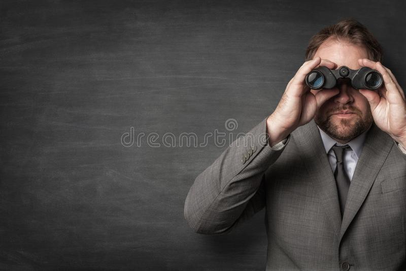 Affärsman i en dräkt som håller ögonen på med kikare arkivfoton