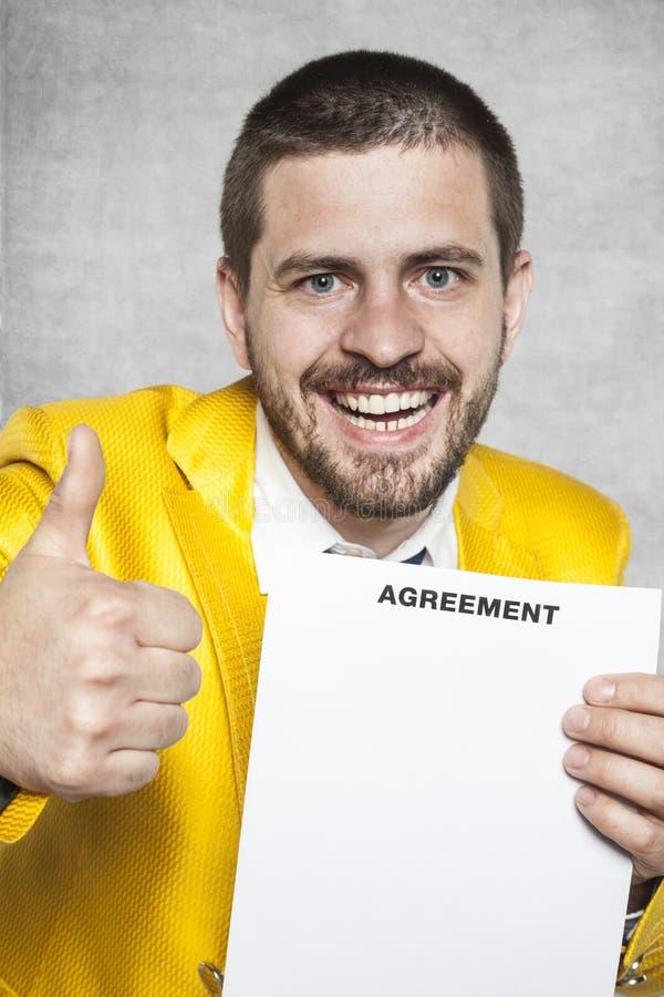 Affärsman i en guld- dräkt och tummar upp, den nya överenskommelsen arkivbild