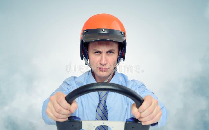 Affärsman i en hjälm med styrninghjulet royaltyfri bild