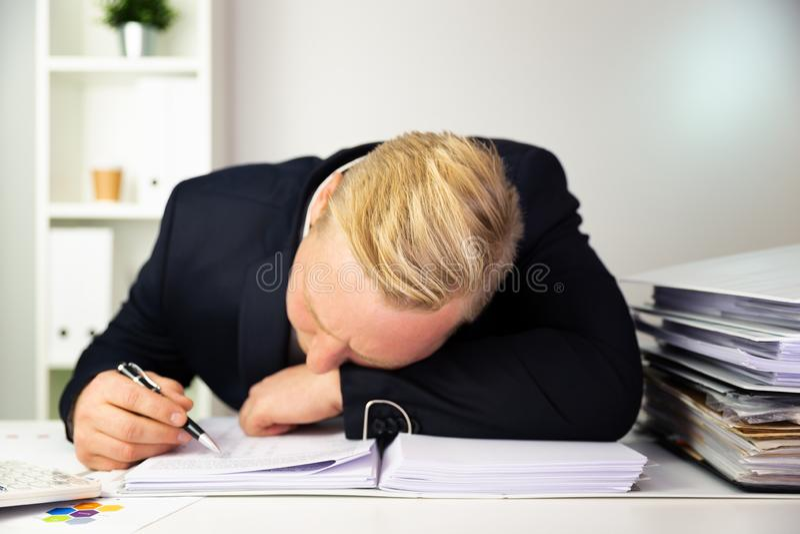 Affärsman i ett mörkt - blå dräkt som beräknar försäljningsresultat finan arkivbild
