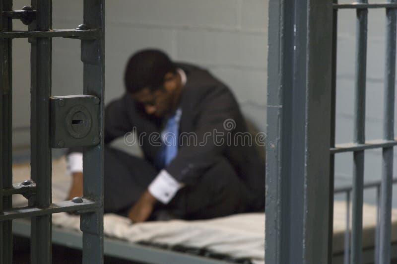 Affärsman i fängelsecell royaltyfri bild