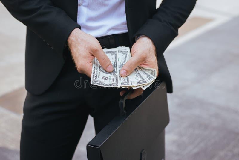 Affärsman, i för pengarUS dollar för dräkt hållande räkning och att räkna arkivbilder