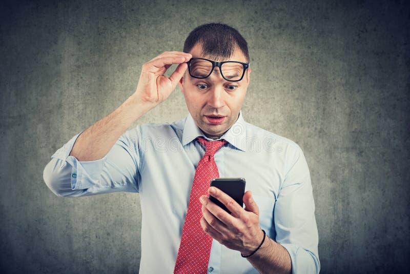 Affärsman i glasögon som håller ögonen på smartphonen i chockläsningmeddelande royaltyfri foto