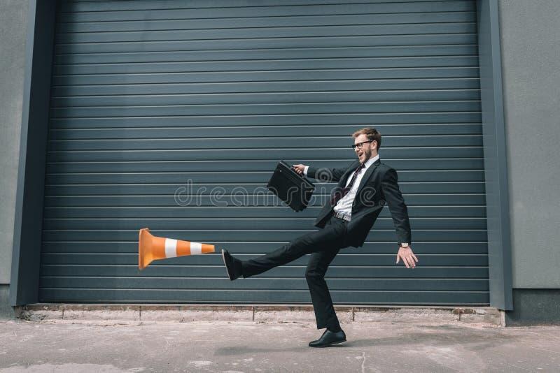 Affärsman i glasögon som rymmer portföljen och sparkar trafikkotten arkivfoton
