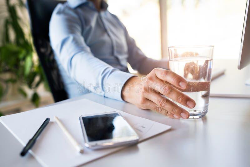 Affärsman i hans kontor, smartphone och exponeringsglas av vatten royaltyfri foto
