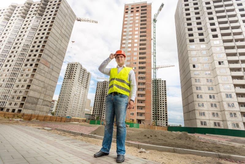Affärsman i hardhat- och säkerhetsvästanseende på byggnadsplats royaltyfria foton