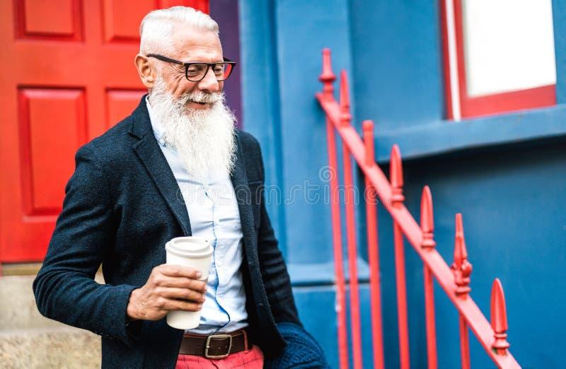 Affärsman i Hipster som går med en kaffeväggsbakgrund - Trendy gammal person som har tillfälliga modekläder arkivfoto