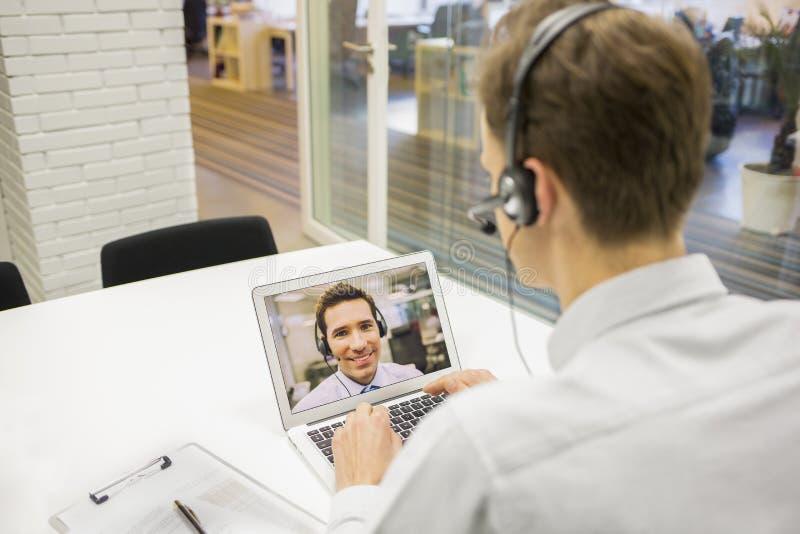 Affärsman i kontoret på videokonferens med hörlurar med mikrofon, Skype fotografering för bildbyråer