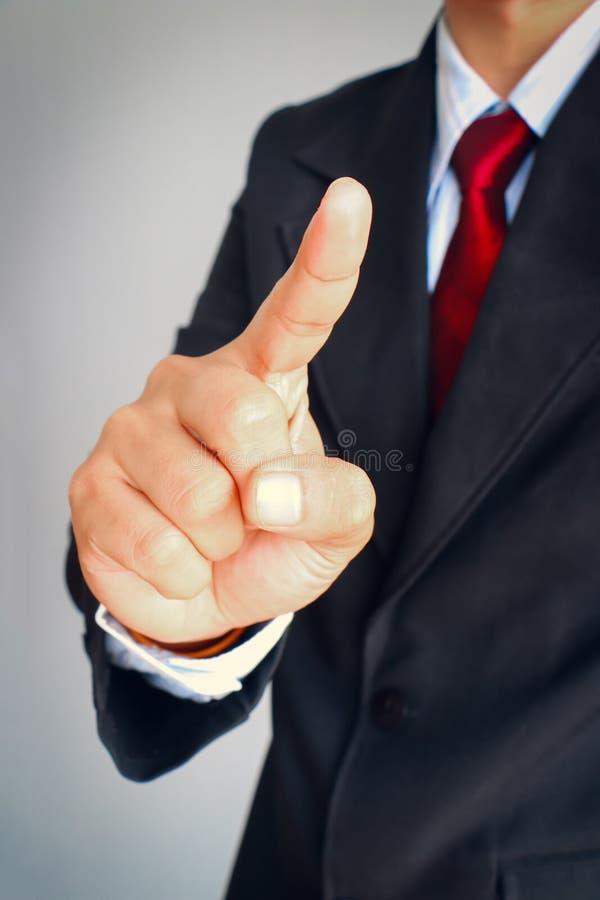 Affärsman i punkt för dräktvisninggest något royaltyfri foto