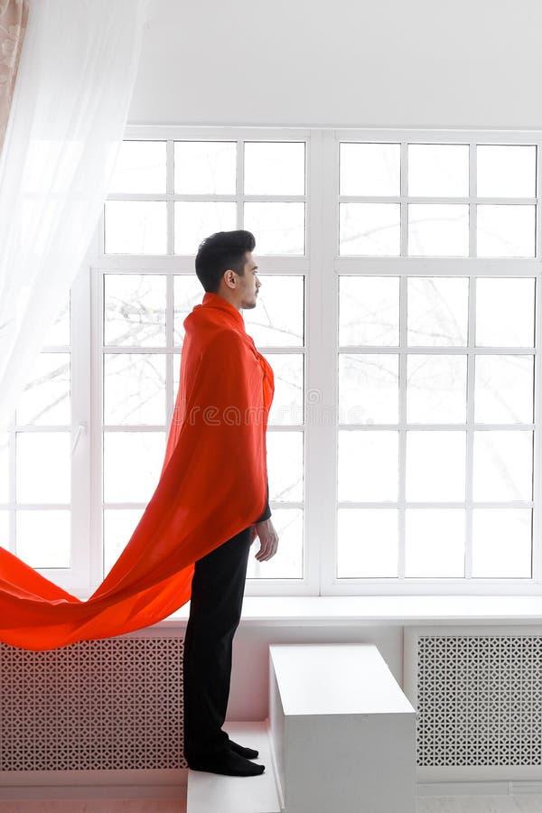 Affärsman i röd superherokappa Ung man i dräkt- och stålmanudde på trappa royaltyfria foton