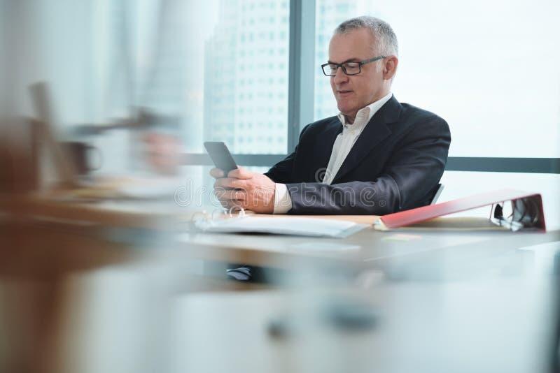 Affärsman i regeringsställning som använder socialt massmedia under arbetstid arkivbild