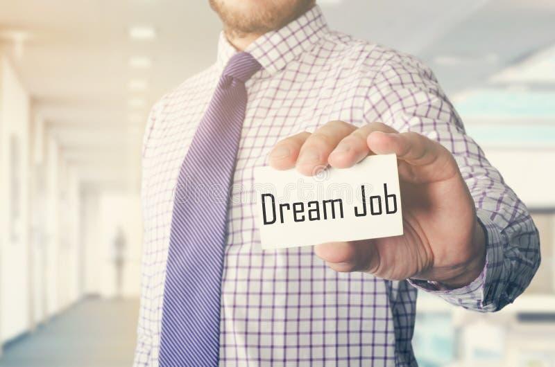 affärsman i regeringsställning som visar kortet med text: Dröm- jobb arkivfoto