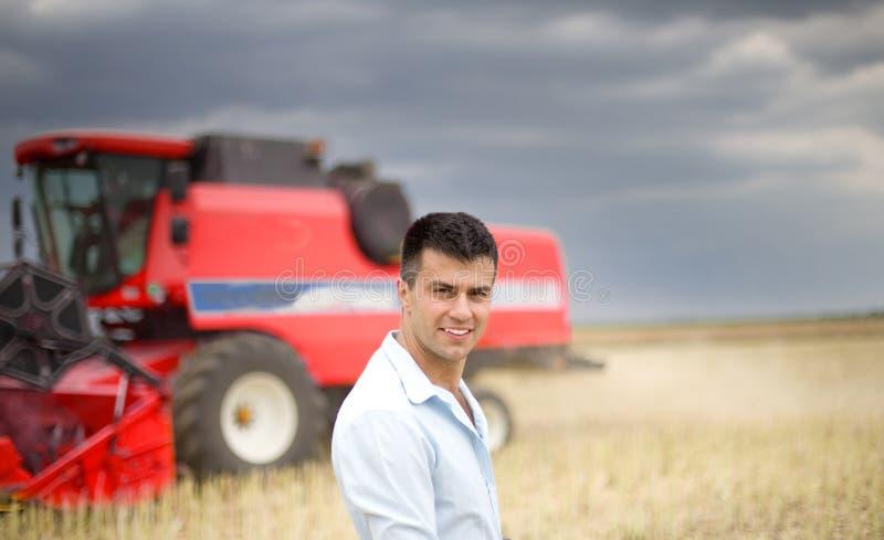 Affärsman i sojabönafält Skördetröska i bakgrund arkivfoton