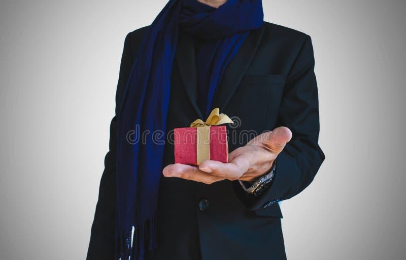 Affärsman i tillfällig dräkt med den lilla gåvaasken förestående, selektiv fokus på gåvaasken fotografering för bildbyråer