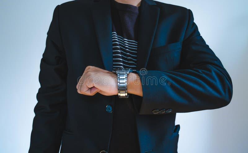 Affärsman i tillfällig dräkt som håller ögonen på en klocka arkivbild