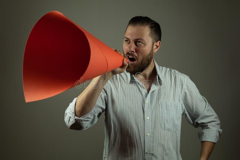 Affärsman i tillfällig skjorta som meddelar något på en megafon som göras av papper royaltyfri foto