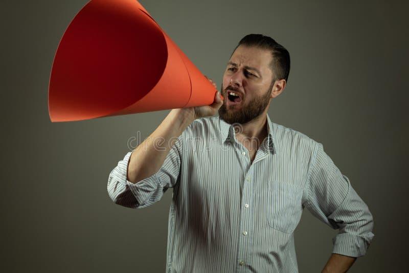 Affärsman i tillfällig skjorta som meddelar något på en megafon som göras av papper royaltyfria foton