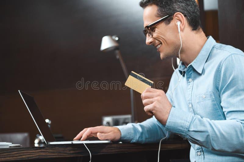 affärsman i tillfälliga kläder för affär som rymmer hans kreditkort, medan genom att använda bärbara datorn royaltyfria foton