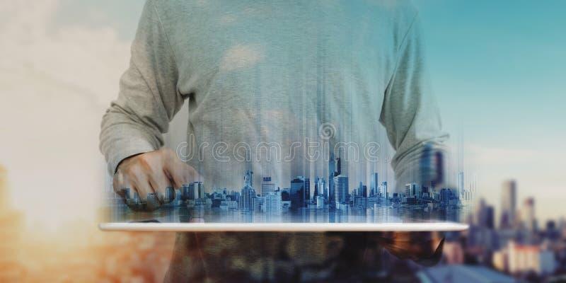 Affärsman i tillfälliga kläder genom att använda den digitala minnestavlan, med futuristiska moderna byggnader för hologram Fasti royaltyfri fotografi