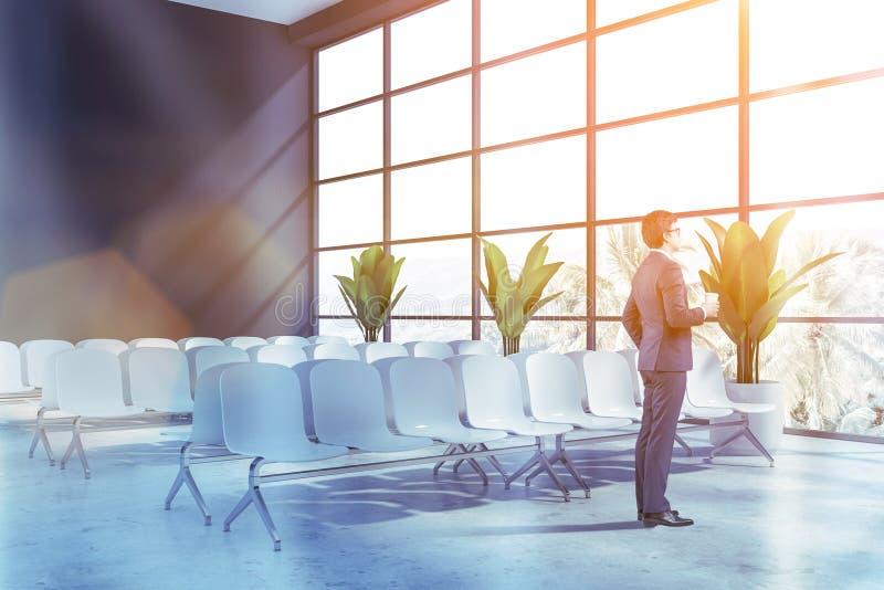 Affärsman i väntande rum för grå flygplats arkivfoton