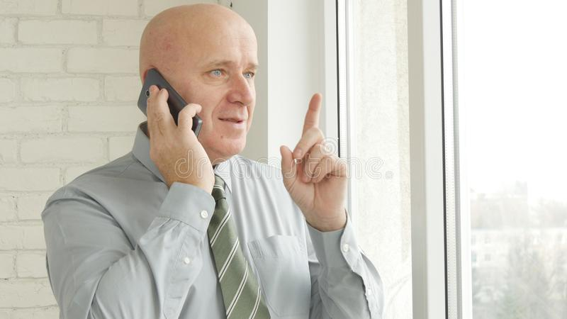 Affärsman Image Talking till mobilen som pekar med fingret upp royaltyfri bild