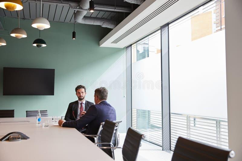 Affärsman Interviewing Male Candidate på den doktorand- rekryteringbedömningdagen i regeringsställning royaltyfria bilder