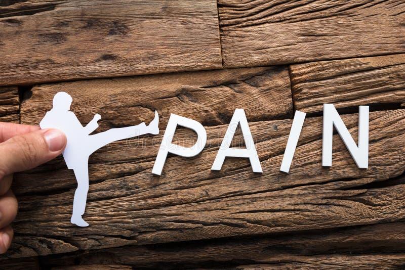 Affärsman Kicking Word Pain för handinnehavpapper fotografering för bildbyråer