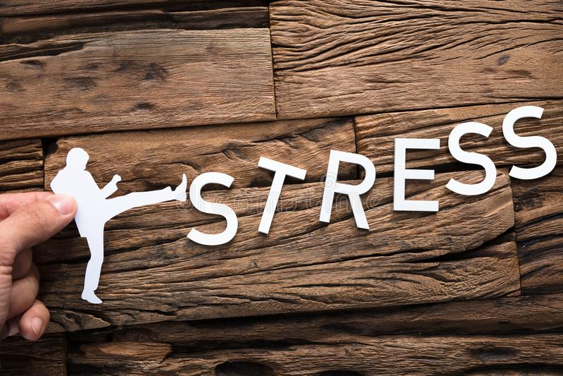 Affärsman Kicking Word Stress för handinnehavpapper royaltyfri bild